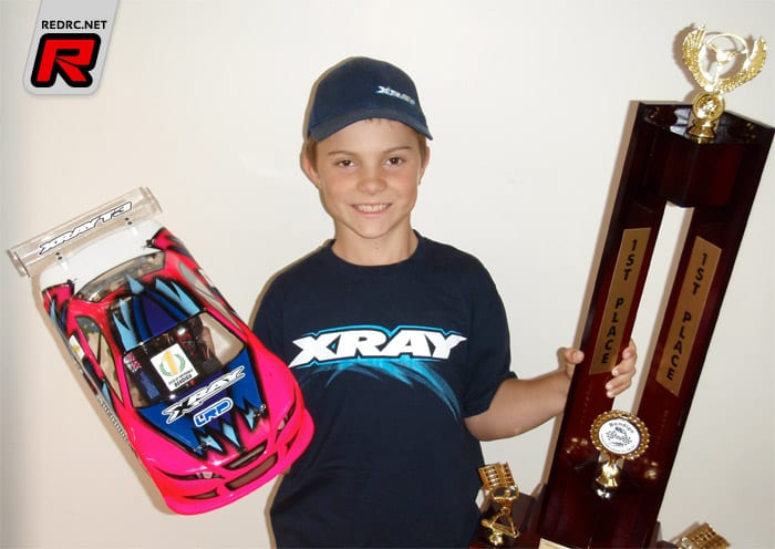 A very young Piastri poses with his X-Ray r/c car and winners trophy
